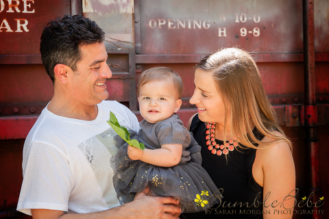 fun casual portrait of dad, mom and baby