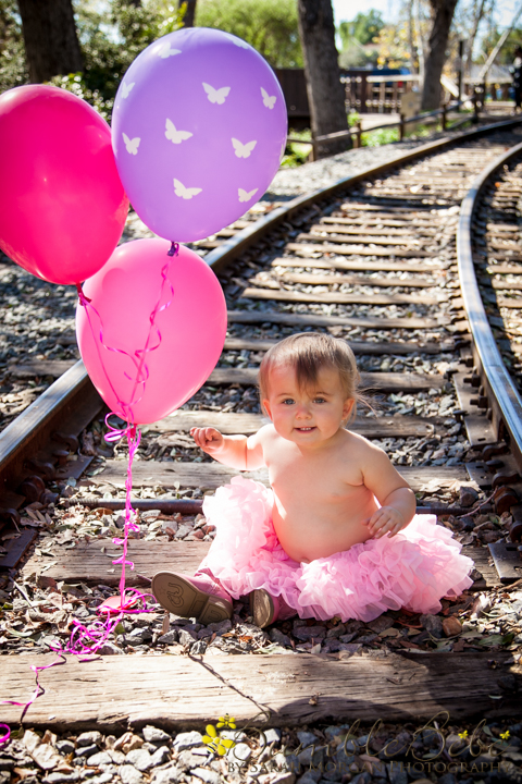 Baby Riley on the train tracks with her balloons
