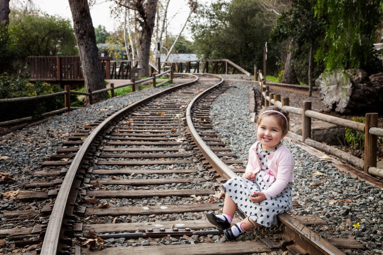 adorable little girl on train tracks in Old Poway Park