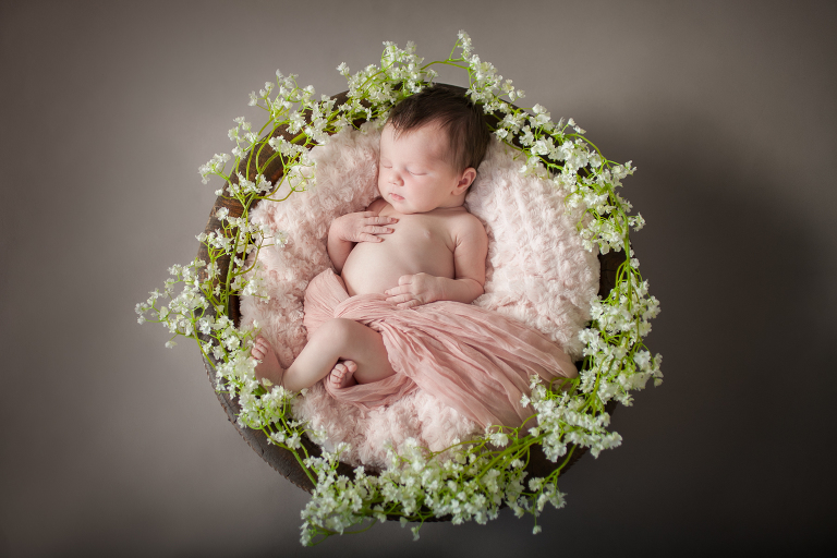 newborn baby in bowl surrounded by flowers