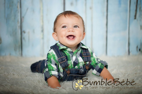 Baby Elliott smiles during his 9 month old portraits